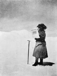 "Fanny Bullock Workman, holding a ""Votes for Women"" newspaper at 21,000 ft in the Karakoram"